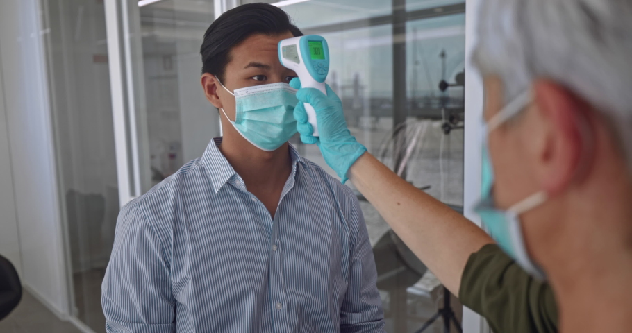 Man with covid mask checking temperature before work in office Royalty-Free Stock Footage #1060360160