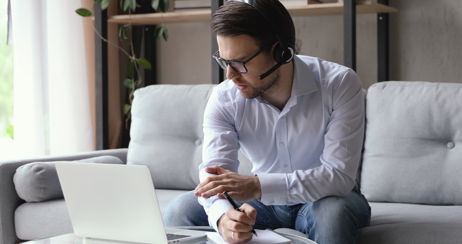 Focused young businessman in glasses wearing headset with mic, holding video call project negotiations with partners or clients, writing down notes in copybook, discussing working issues remotely.