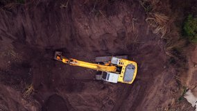 Crawler excavator working at the construction site. Construction machinery for excavating, loading, lifting and hauling of cargo on job sites. Aerial top view, 4K Video