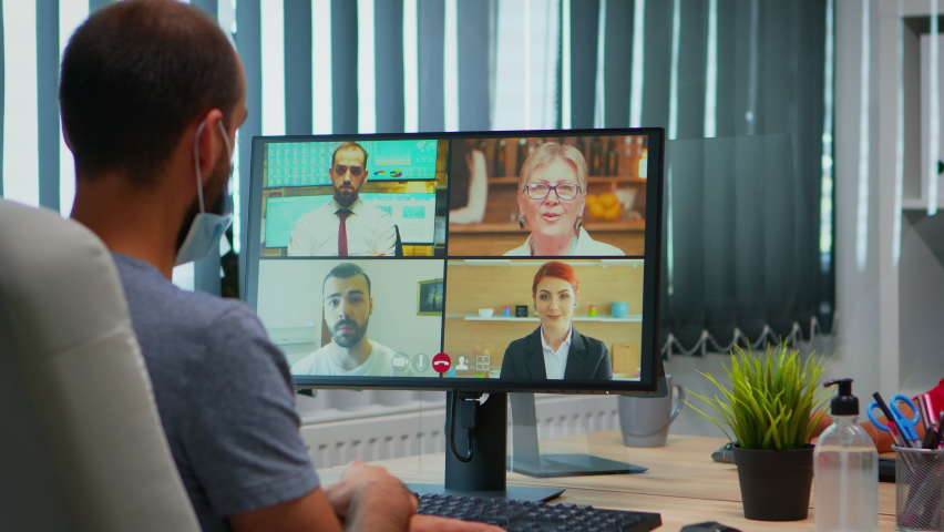 Back view of man with mask talking on video call with remotely colleagues. Freelancer working in new normal office workplace chatting during virtual conference, meeting, using internet technology Royalty-Free Stock Footage #1060362578