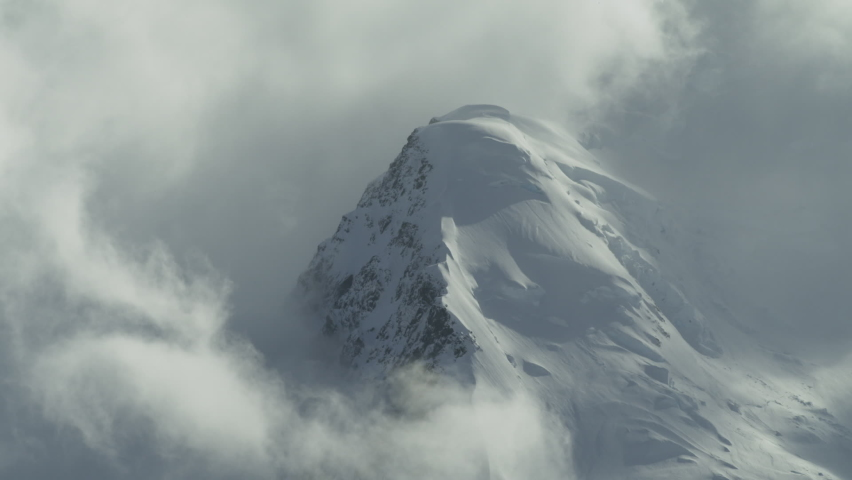 Clouds float around a snowy mountain peak