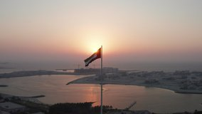 Flag of United Arab Emirates waving in the wind with sun setting behind during sunset in Dubai; silhouette video of UAE flag