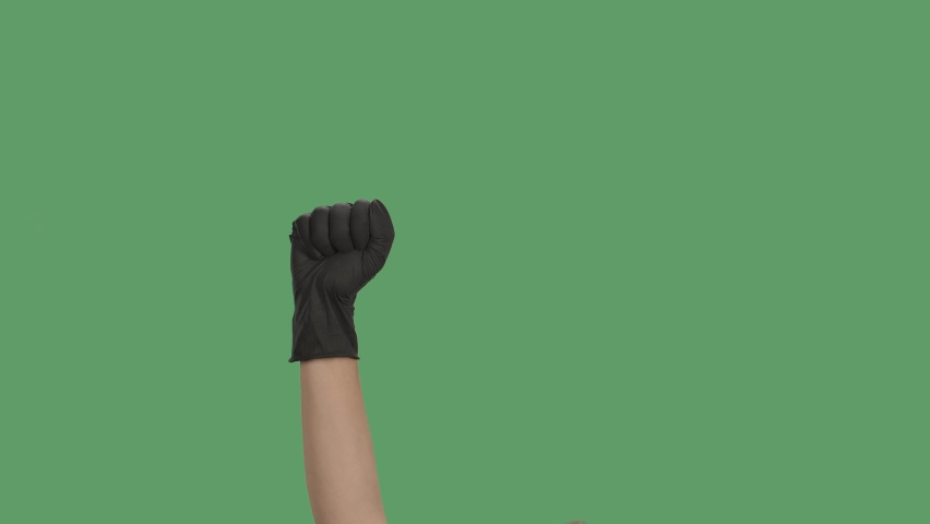 Raised hand in black gloves with clenched fist for protest on green screen chroma key background. Cropped shot of protester raising arm clenching fist at political demonstration. Close up. Slow motion