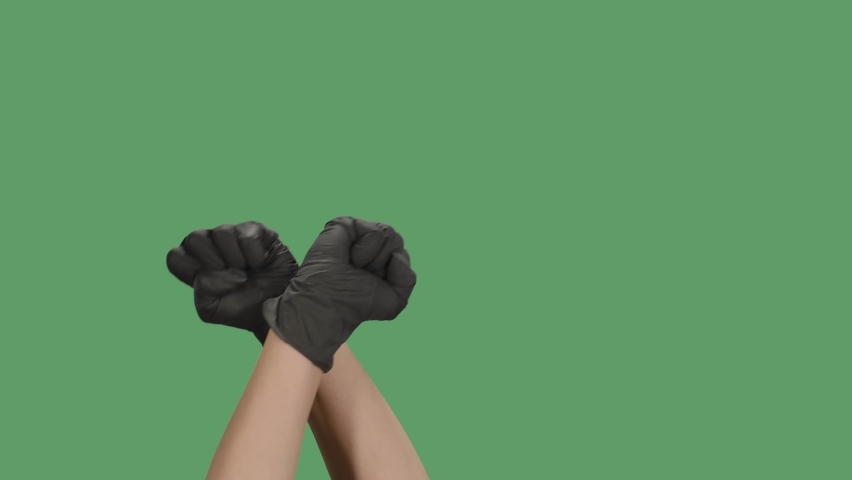 The raised clenched fists is a hand gesture symbol of solidarity, support, salute to express unity, strength. Black Lives Matter. Isolated a green screen, chroma key. Close up. Slow motion.