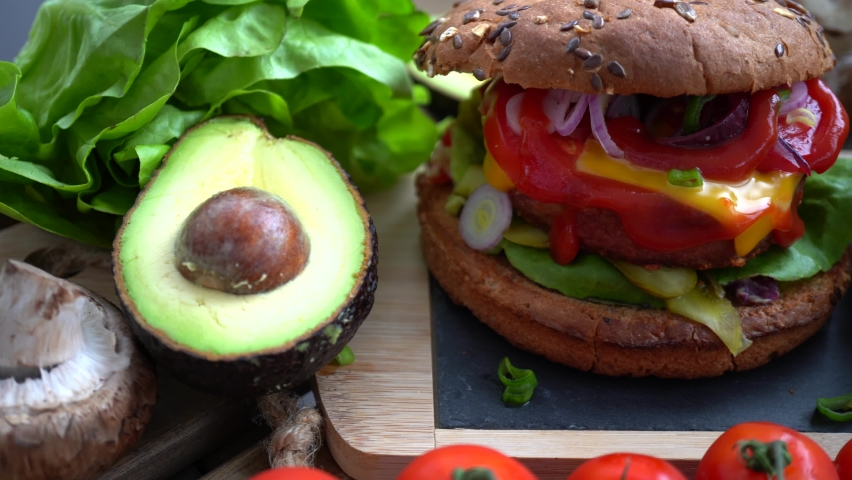 Vegan or vegetarian burger with patty from impossible meat as an alternative to classic hamburger | Shutterstock HD Video #1060380881