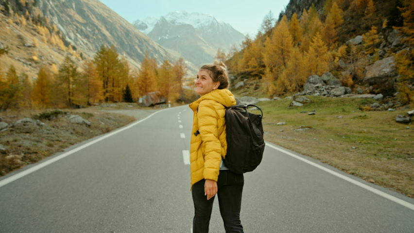 Camera follows woman on trip or adventure. Young millennial traveller or travel blogger walk in beautiful mountain valley and make photos for social media or memories. Generation z new concept travels | Shutterstock HD Video #1060381955