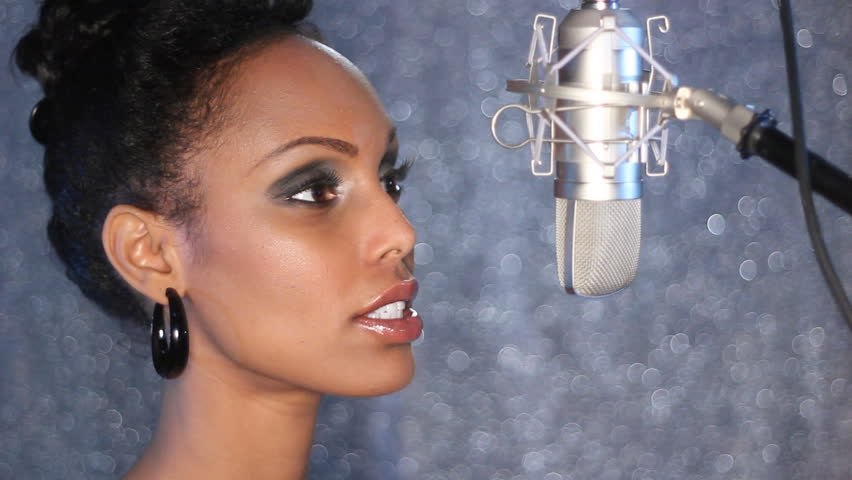 Studio singer.  Attractive young woman sings into a professional, condenser microphone.
