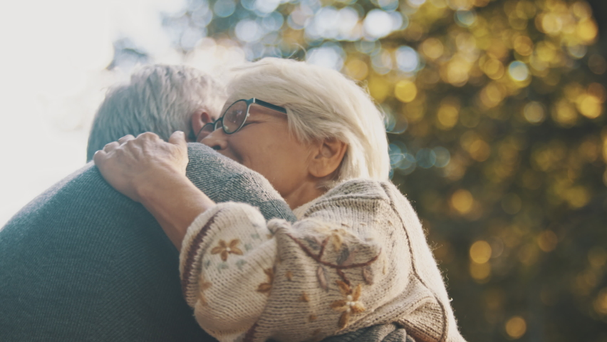 Elderly couple in love embracing in the park on an autumn day. High quality 4k footage | Shutterstock HD Video #1060391606
