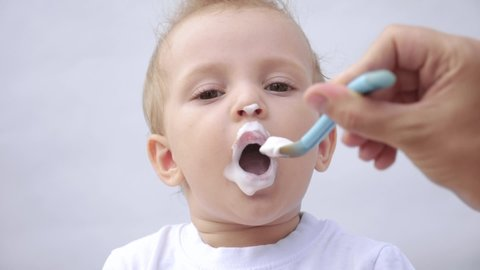 newborn baby eats from a spoon, close-up portrait grimy face. newborn baby at home kid dream concept. Newborn baby son gets dirty and eats with pleasure. baby and mom fun at home