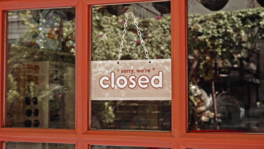 A sign hanging on the door of the institution with a glass window with the inscription closed Royalty-Free Stock Footage #1060396634