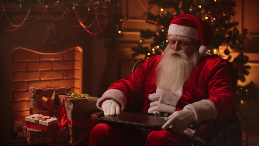 Santa Claus warm atmosphere in living room using laptop. | Shutterstock HD Video #1060396904