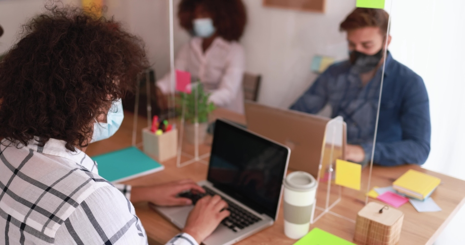 Multiracial co-workers using tablet and laptop inside creative office during coronavirus outbreak - People wearing protective masks while working behind safety plexiglass Royalty-Free Stock Footage #1060398695