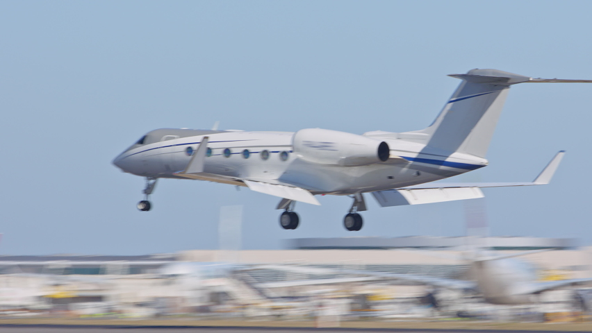 Generic Unmarked Executive Business Private Jet Airplane Landing at International Airport near Lisbon Portugal Touching Down on Runway with Tire Smoke on a Sunny Day in Europe | Shutterstock HD Video #1060402076