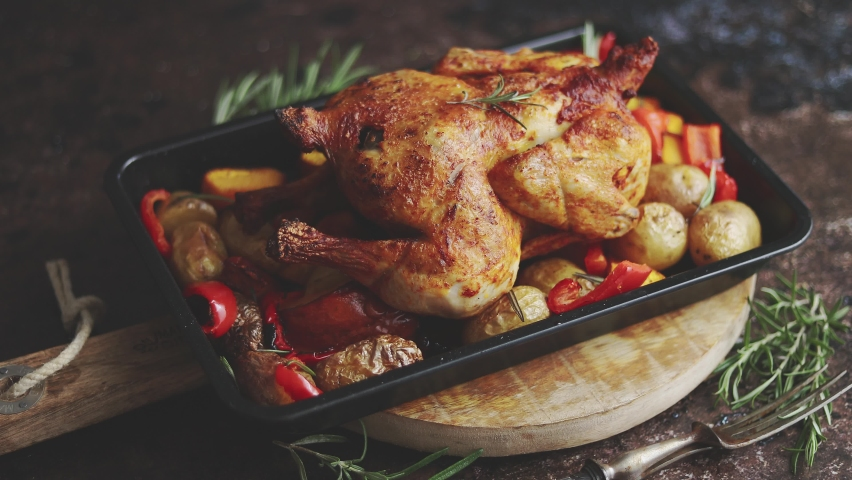 Whole roasted chicken or turkey with pumpkin, potatoes, red pepper and rosemary. Served in metal baking dish. | Shutterstock HD Video #1060414633
