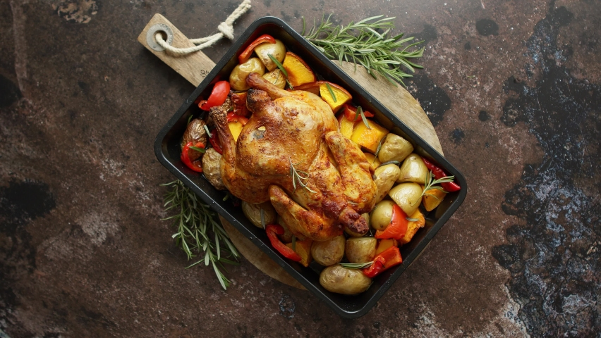Delicious whole chicken cooked with pumpkin, pepper and potatoes. Served in metal baking pan. Decorated with rosemary. Autumn food concep. Top view. Flat lay. | Shutterstock HD Video #1060414645