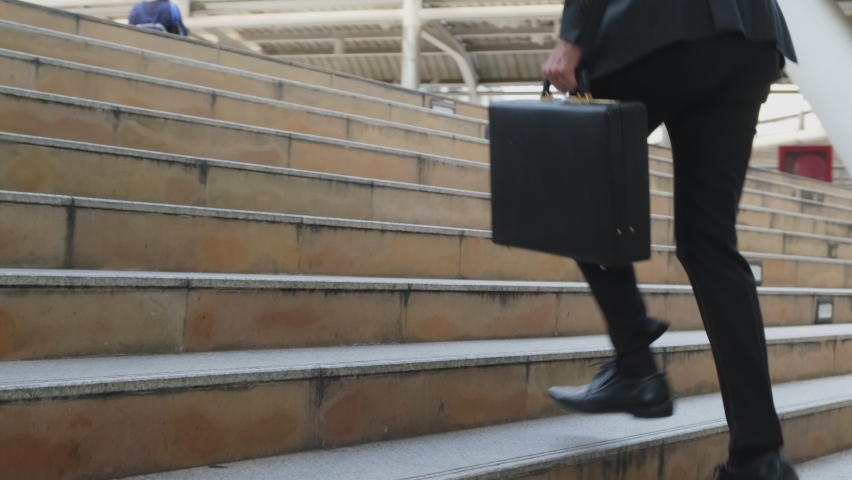 Close up shot of hurry Asian young businessman running up on stair going to work in office. The working man holding business handbag with office formal suit walking outdoor in urban city. Royalty-Free Stock Footage #1060426792