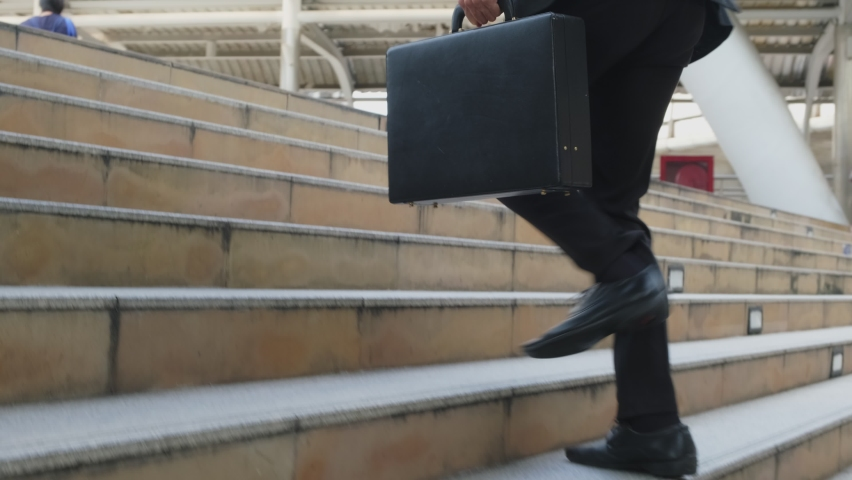 Close up shot of hurry Asian young businessman running up on stair going to work in office. The working man holding business handbag with office formal suit walking outdoor in urban city.