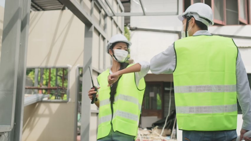 Asian workers people wearing protective face mask onsite of architecture due to covid pandemic crisis. Male and female engineers making elbow touch instead of handshake to avoid coronavirus infection. Royalty-Free Stock Footage #1060426828