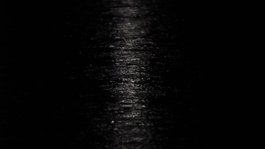 Reflection of a beam of light at night on the asphalt during the rain. A vertical narrow strip of light on a black background. Ripples from drops on the water surface. UHD.