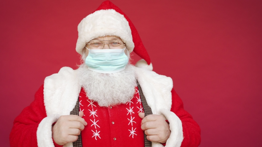 Portrait of funny happy old bearded Santa Claus recommend wearing face mask looking at camera showing thumbs up standing on Merry Christmas red background. Covid 19, coronavirus safety protection.