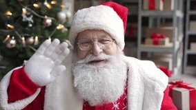 Funny old bearded Santa Claus, Saint Nicholas talking to camera greeting on Merry Christmas Happy New Year, standing in warehouse workshop, video calling by webcam online virtual chat concept.