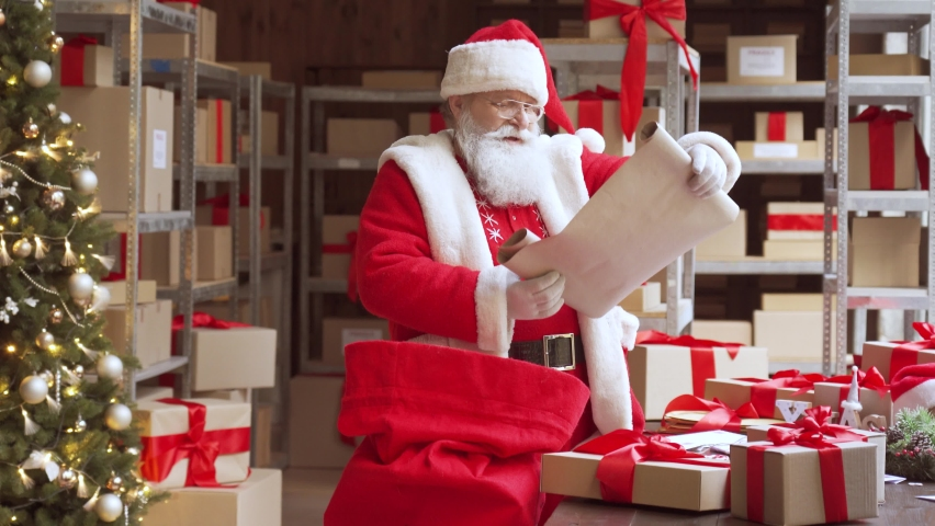 Old funny Santa Claus, Saint Nicholas packing presents gift boxes in sack bag preparing post shipping fast xmas delivery parcels walking in workshop. Merry Christmas shipping delivery concept.