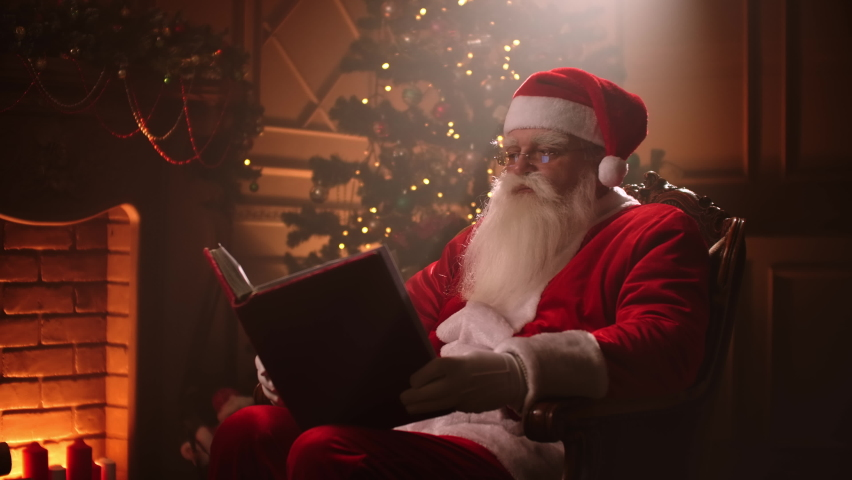 Joyful santa clause sitting in his rocker in decorated room, reading a book with red cover - holiday mood, christmas spirit concept. | Shutterstock HD Video #1060457374