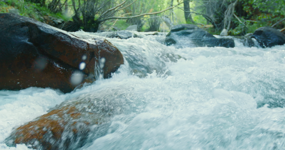 Nature shot. Fresh water slow motion. Rapid water flows between the wet stones in wooden forest with lavish green trees. Water splashes, drops and bubbles puled out of the mountain river, slow motion   Shutterstock HD Video #1060462429