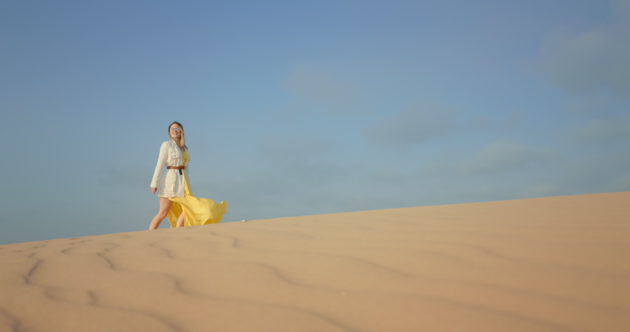4K slow motion footage with blue space for copy or text on background for commercial usage. Cinematic shot of woman in stylish outfit walking by wavy sand surface. Scenic wild nature landscape view | Shutterstock HD Video #1060462474