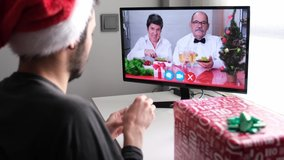 Senior couple celebrating new year eating grapes with their son on a video call. Spanish new year tradition. Christmas celebration concept.