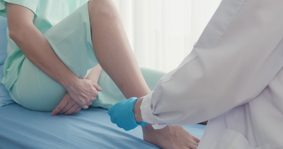 The doctor is first aid for the leg injured patients. The doctor is wrapping the leg bandage to the patient. | Shutterstock HD Video #1060470619