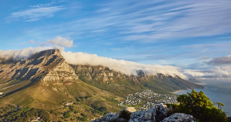 4k right to left panning time elapse of rolling clouds over table top mountain at sunset and the city of Cape Town,South Africa