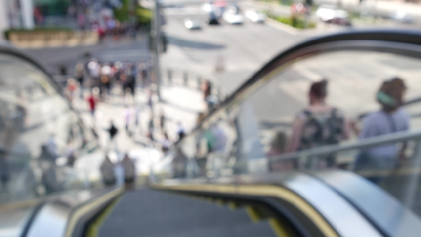 Perspective view thru escalator, defocused unrecognizable group of people on road intersection crosswalk on Strip of Las Vegas, USA. Anonymous blurred pedestrians on walkway in crowded urban downtown. | Shutterstock HD Video #1060474984