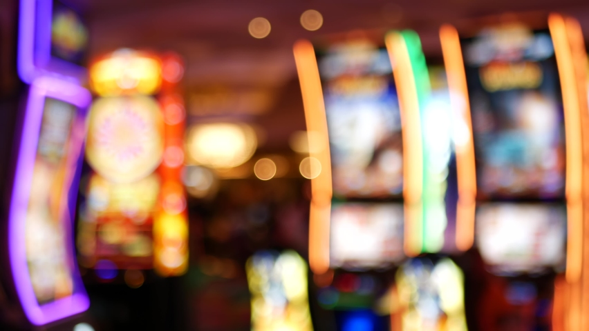 Defocused slot machines glow in casino on fabulous Las Vegas Strip, USA. Blurred gambling jackpot slots in hotel near Fremont street. Illuminated neon fruit machine for risk money playing and betting. | Shutterstock HD Video #1060475005