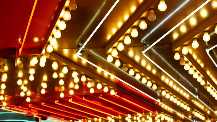 Defocused old fasioned electric lamps glowing at night. Abstract close up of blurred retro casino decoration shimmering, Las Vegas USA. Illuminated vintage style bulbs glittering on Freemont street. | Shutterstock HD Video #1060475008