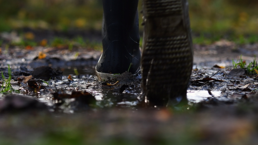 Feet with rain boots walking in puddles and dirt. Autumn colors and fallen leaves on the ground. Walking away from camera.  Royalty-Free Stock Footage #1060477033
