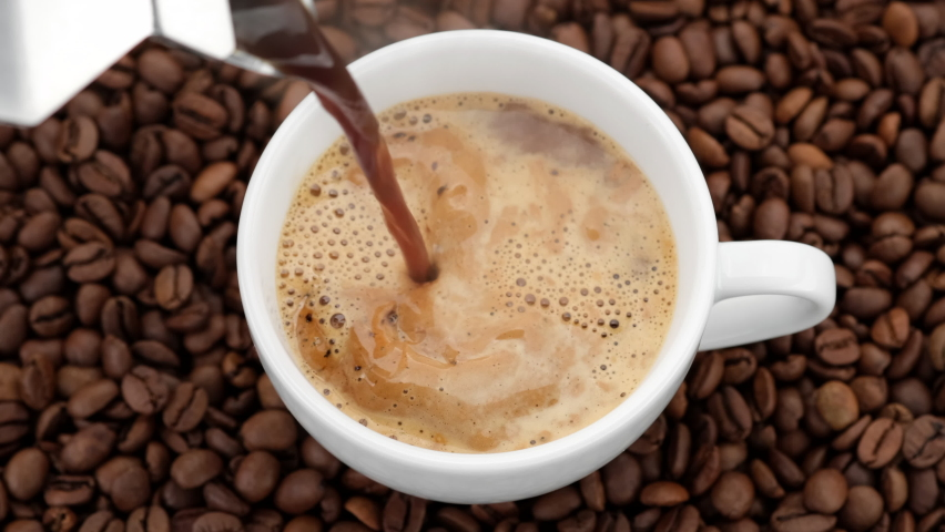 Pouring black coffee in cup. top view of coffee pour into cup from geyser coffee maker. coffee with froth | Shutterstock HD Video #1060480036