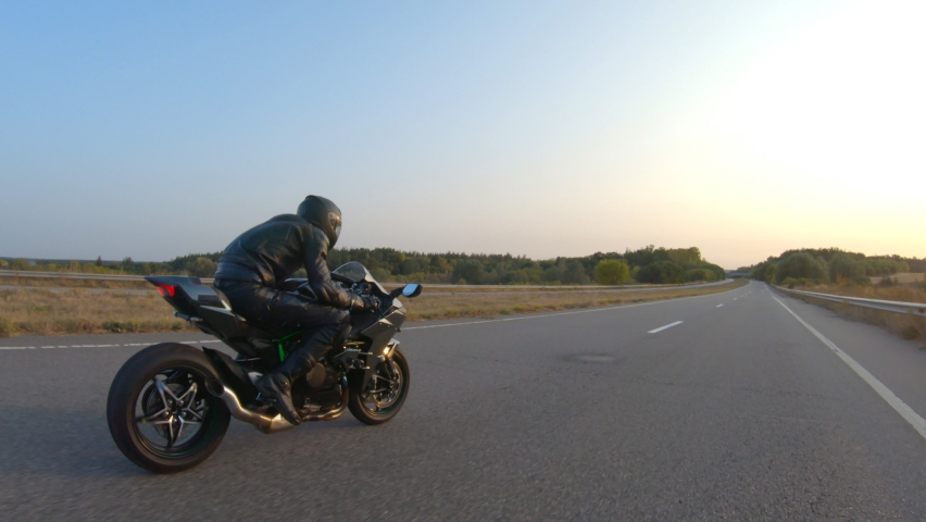 Aerial shot of man riding fast on modern sport motorbike at highway during sunset. Motorcyclist racing his motorcycle on country road. Guy driving bike during trip. Concept of freedom and adventure | Shutterstock HD Video #1060484599