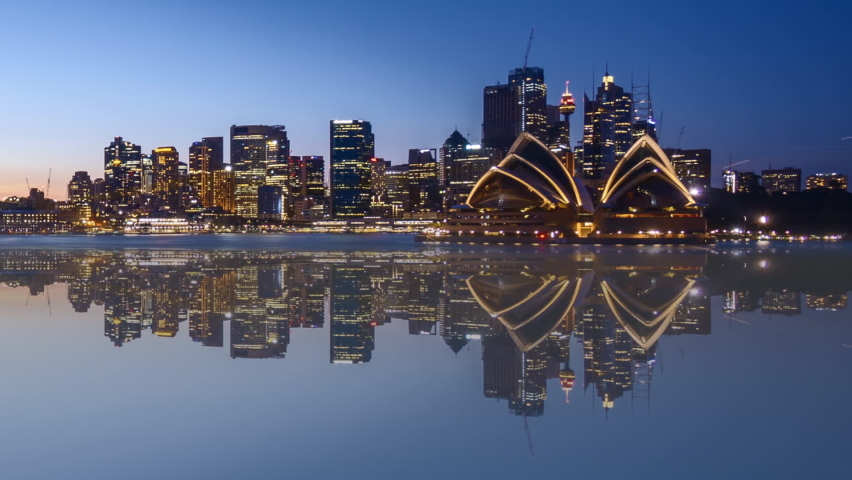 Time lapse of beautiful city skyline with water reflection effect, from sunset to sunrise (day to night to day). Pan right