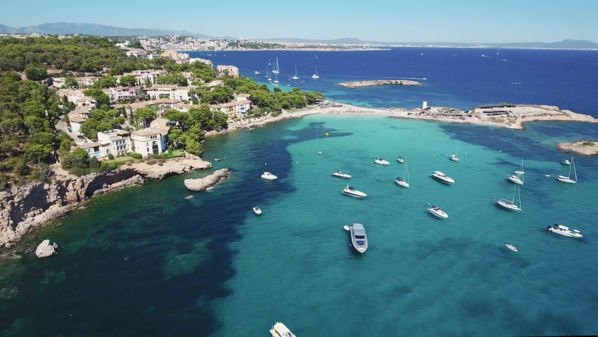Beautiful aerial view of yachts and boats anchoring in a bay in Mallorca with clear turquoise water - Mediterranean Sea - Spain holiday - Beach in Majorca