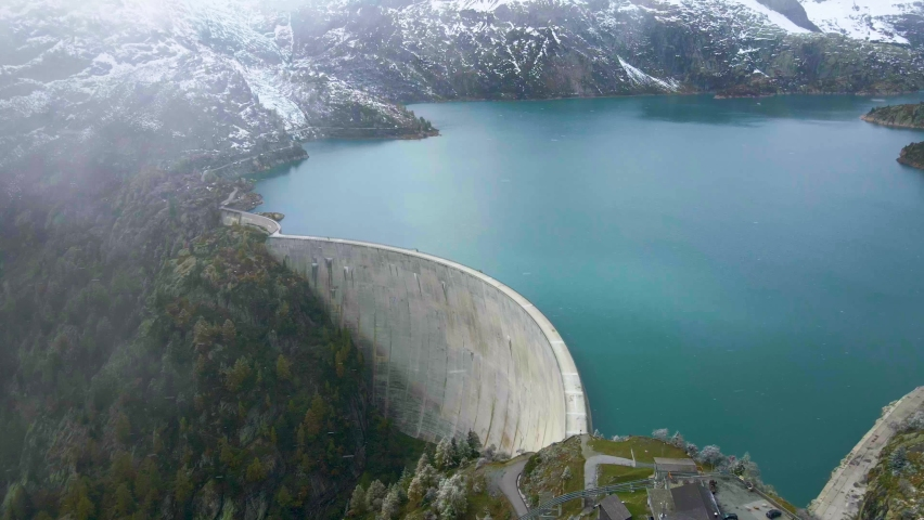 Arch dam and reservoir lake in Swiss Alps mountains feeding hydropower electric power plant to produce renewable energy, sustainable hydroelectricity, snowy weather, aerial drone footage 4K 60 fps Royalty-Free Stock Footage #1060488880