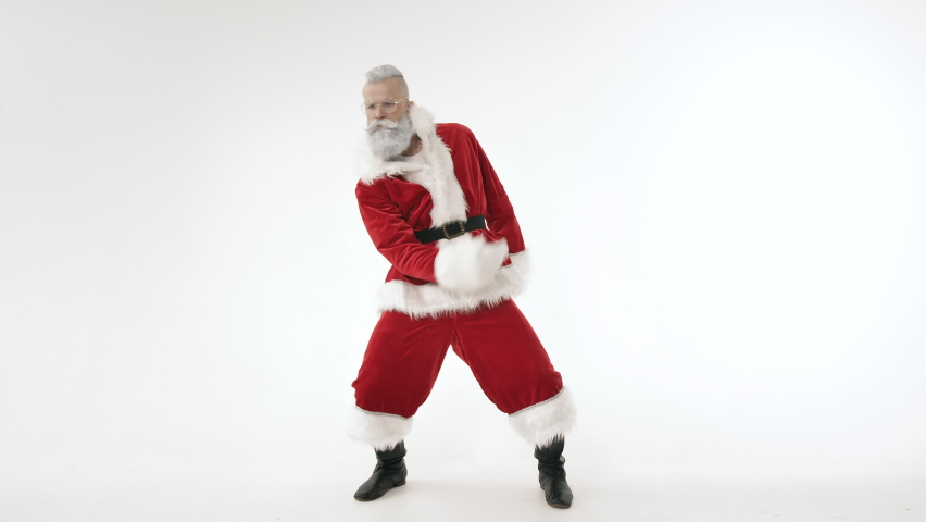 Active Cheerful Stylish Santa Claus Positively Dances, Haves Fun to Energetic Music Looking at Camera, Standing on White Background Indoors. Joyful Celebration Happy New Year, Merry Christmas Holidays