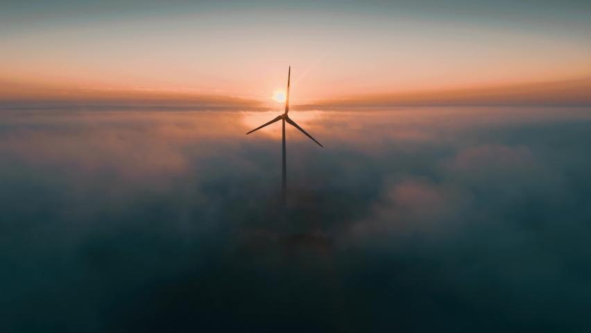 Wind turbine at sunrise in heavy fog. Wind farm generating green energy Royalty-Free Stock Footage #1060491031