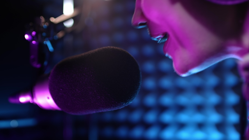 Beautiful young female dj speaks into microphone, records podcast or morning news show for radio. Close up of podcast presenter or DJ talking on the microphone. Wears professional headphones Royalty-Free Stock Footage #1060494403