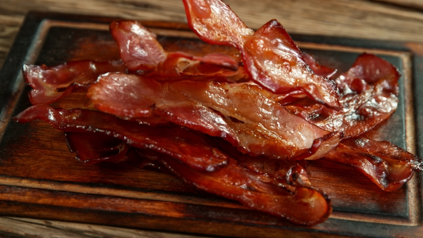 Super Slow Motion Shot of Roasted Bacon Slices Falling on Wooden Board at 1000 fps. Royalty-Free Stock Footage #1060495804