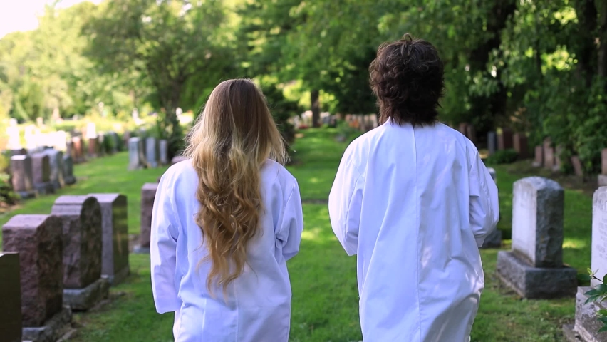 Rear view of two young female walking between tombstones in white long coats while having a conversation in graveyard surrounded with plants