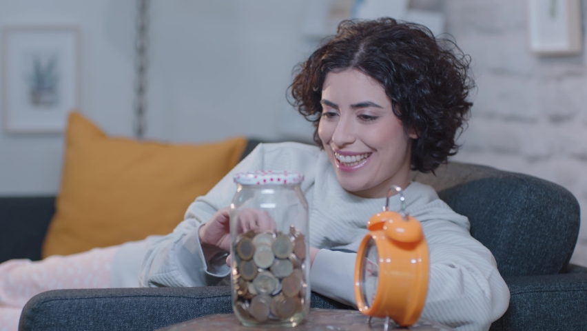 Savings, money saving concept. Young woman is throwing money in the money box. | Shutterstock HD Video #1060499773