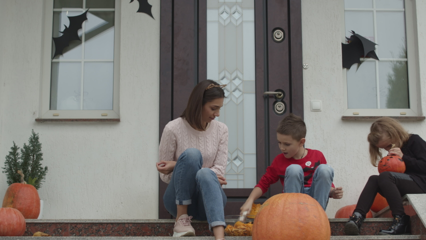 The family is preparing for Halloween on the porch of the house. The boy takes out the insides of the pumpkin. The girl draws a terrible monster.   Shutterstock HD Video #1060500448