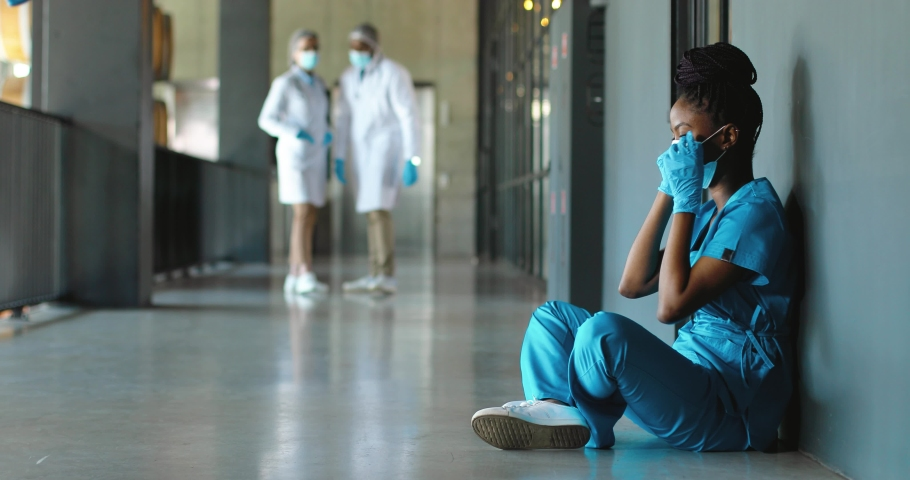 Tired sad African American woman doctor in uniform and gloves taking off medical mask and leaning on wall in despair. Upset female nurse resting, having break. Coronavirus. Rest at work. Covid-19. Royalty-Free Stock Footage #1060503736