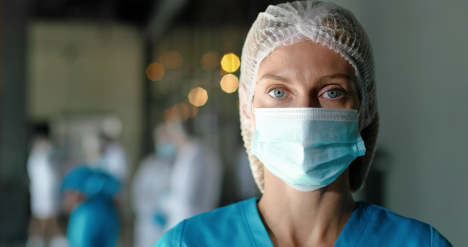 Portrait of tired Caucasian pretty woman doctor in hat and medical mask looking at camera. Close up of female physician. Medic or nurse in clinic. Indoor. Coronavirus concept. Protected. Royalty-Free Stock Footage #1060503742